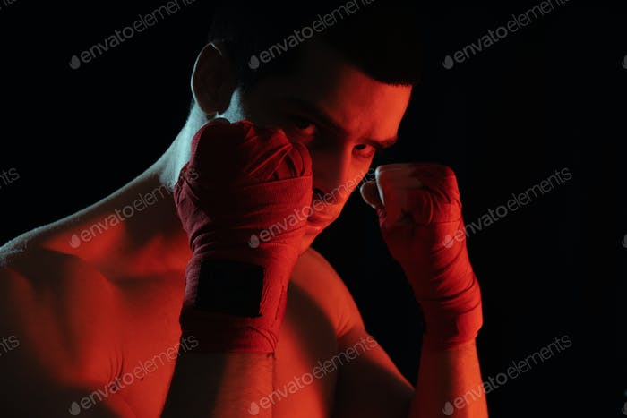 Boxer male fighter posing in confident defensive stance with hands in banndages up