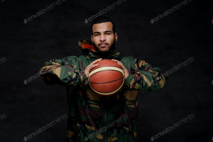 Portrait of a young African-American street basketball player in a camouflage jacket.