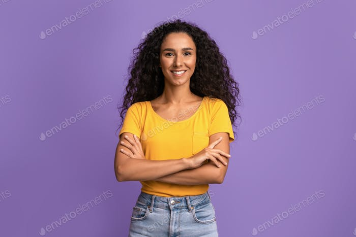 Portrait Of Confident Young Woman Posing With Folded Arms Over Purple Background