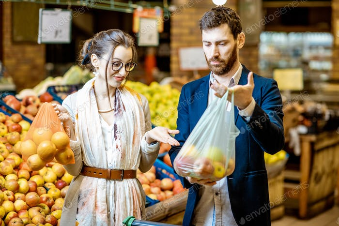 Couple with eco and plastic bag in the supermarket