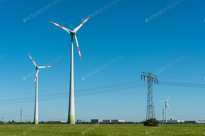 Wind turbines and overhead lines on a sunny day