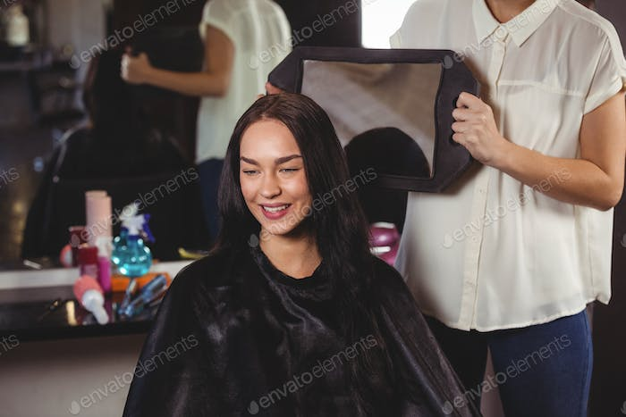 Hairdresser showing woman her haircut in mirror