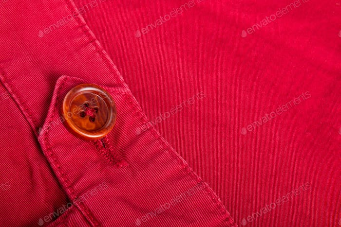 Fragment of red button on cotton twill material. Close up. Copy space.