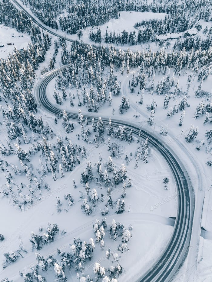 Aerial view winter of road in the forest covered with snow, Finland Lapland