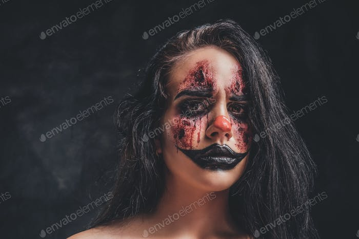 Young woman is playing a role of evil clown