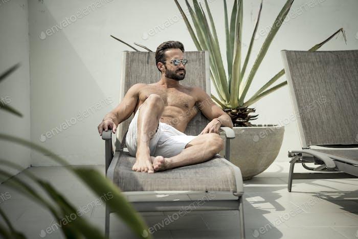 A man lying on a sun lounger.