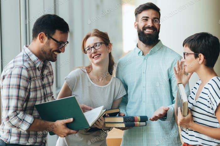 Group of happy young college students studying