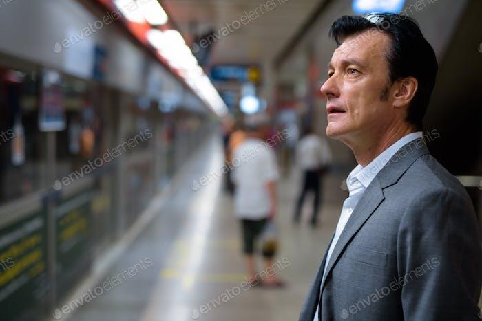 Portrait of mature handsome businessman in train station