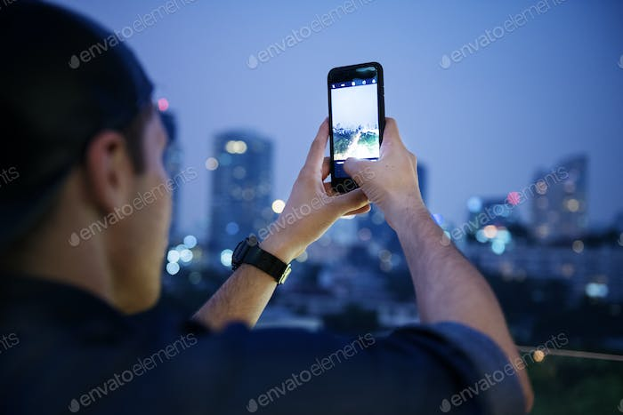 Young man taking a photo of the cityscape from the top of the bu