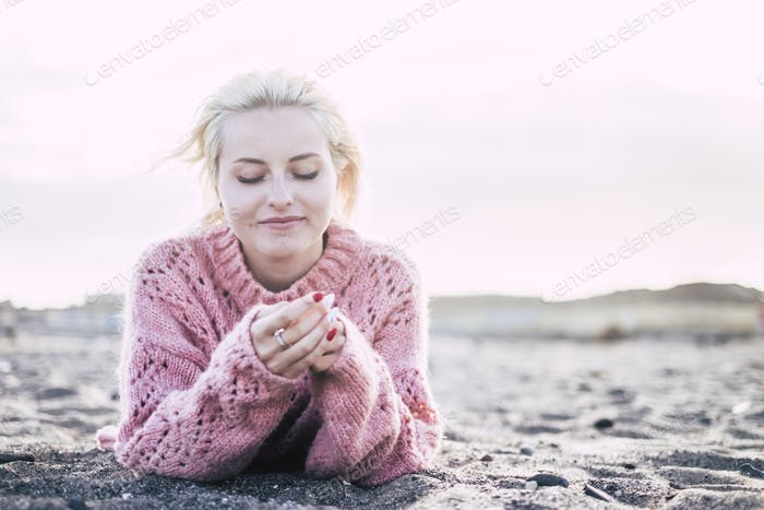 sweet attractive cheerful beautiful young woman lay down on the beach