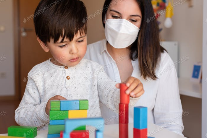 Kid playing with wood blocks and teacher educador help using face mask for coronavirus pandemic.