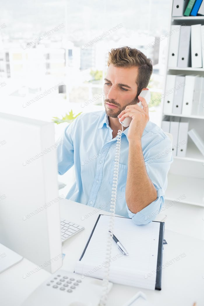 Concentrated male photo editor using phone in a bright office