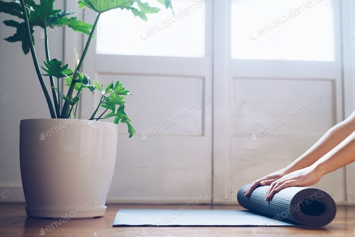Close-up of young woman folding her  yoga mat