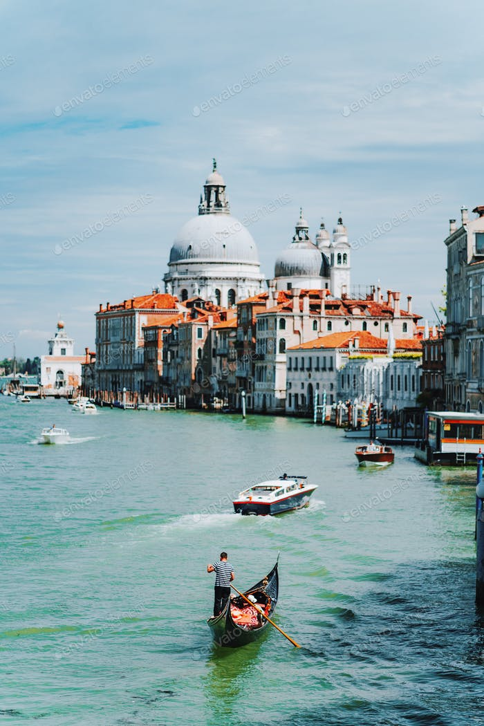 Venice, Italy. Gondola and tourist boats in Grand Canal. Basilica Santa Maria della Salute in