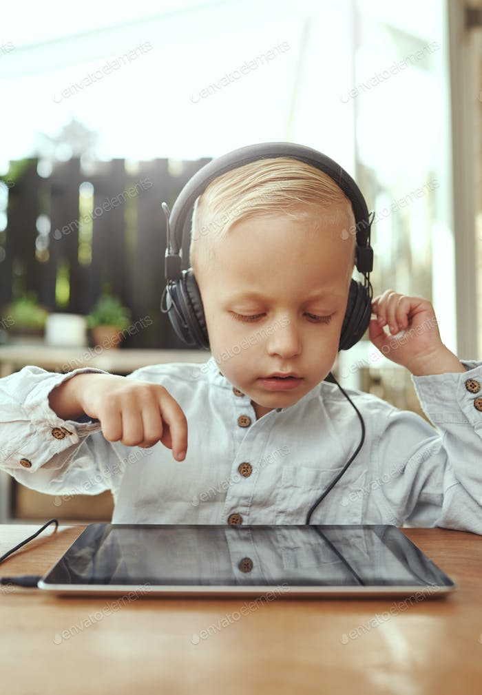 Adorable serious little boy choosing a soundtrack