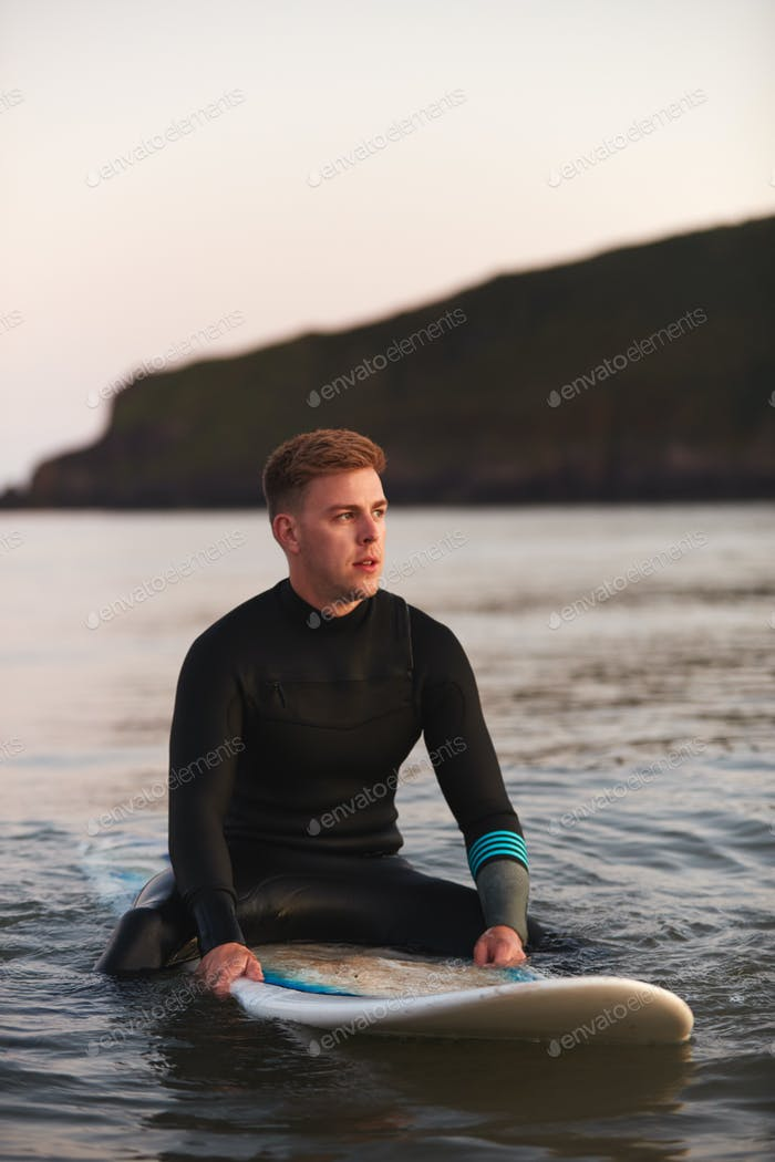 Man Wearing Wetsuit Sitting And Floating On Surfboard On Calm  Sea