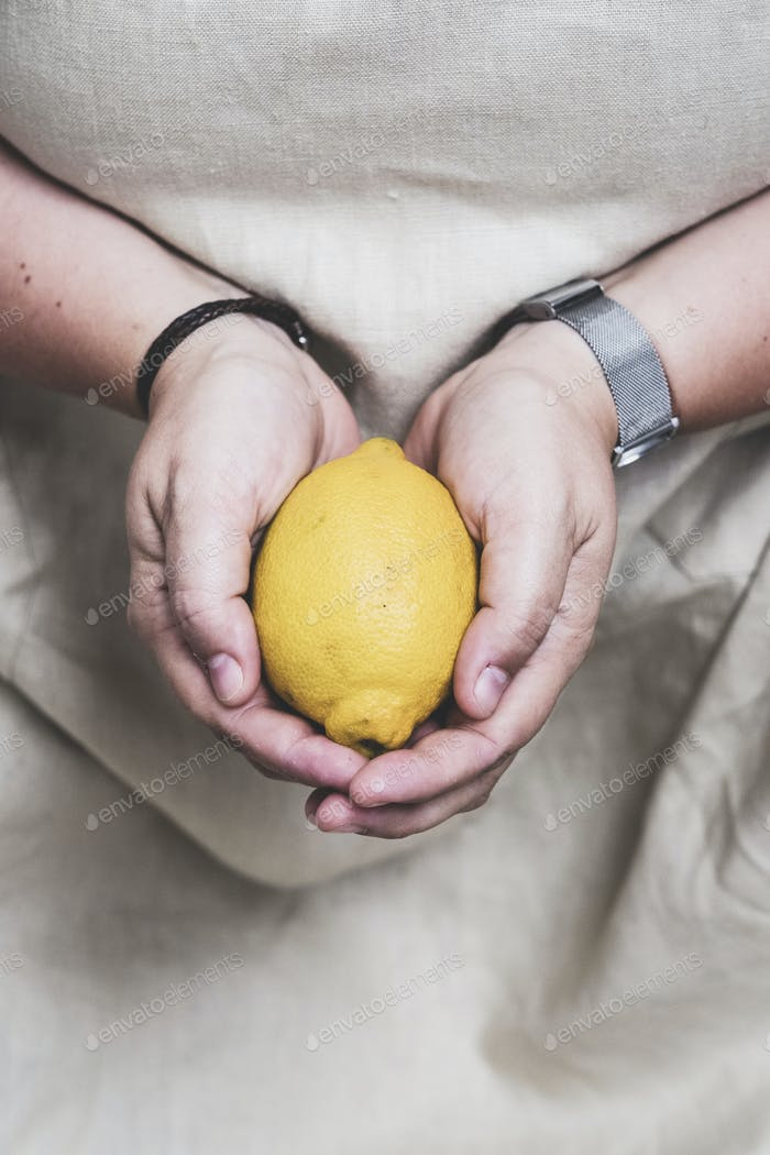Close up of person holding fresh lemon.