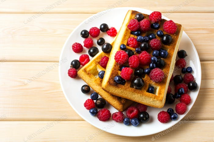 Soft waffle with fresh blueberry and raspberry top view