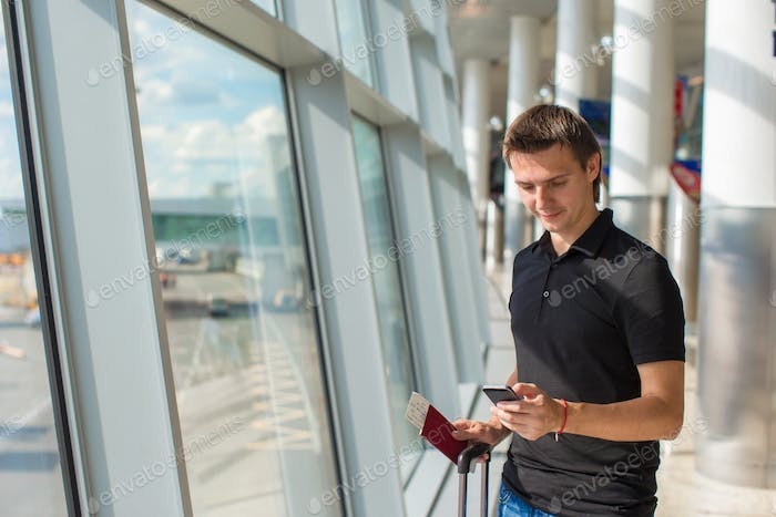 Young man talking on phone inside the airport