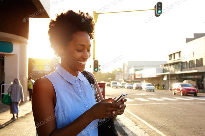 Beautiful african woman using cellphone outdoors