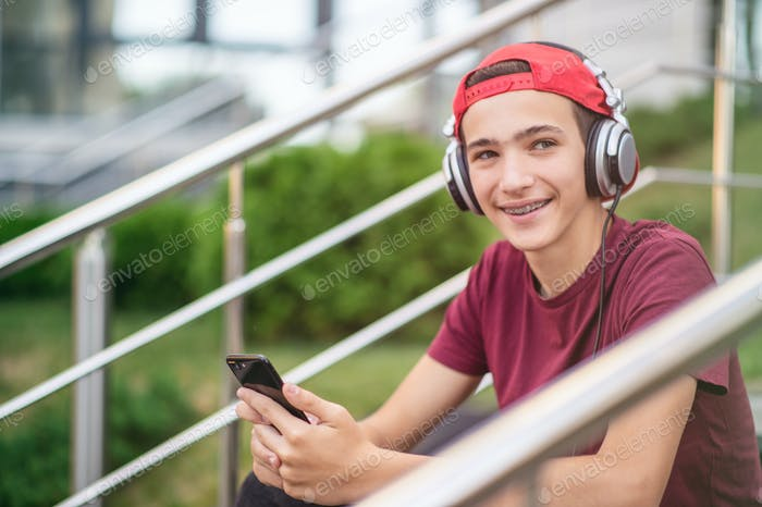 Young man listen to the music in a big earphones, in the street