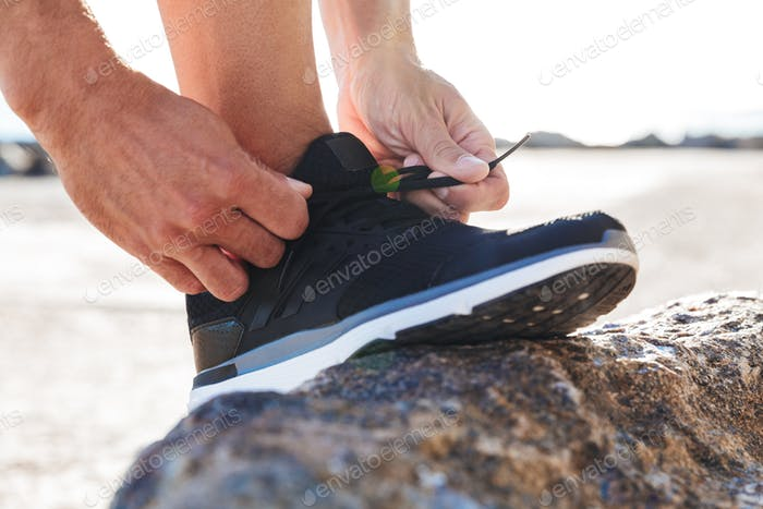 Close up of a man tying tying shoelaces