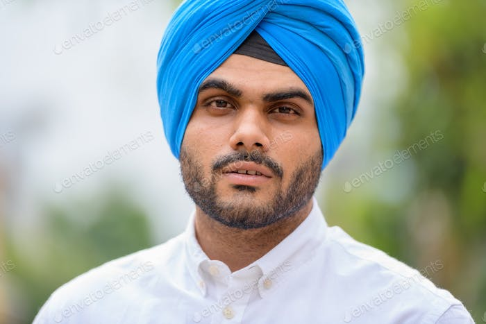 Face of young bearded Indian Sikh man wearing turban outdoors