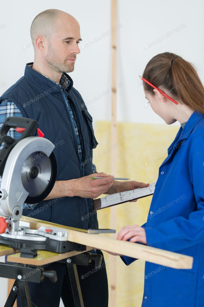 carpentry teacher showing sawing machine to a female student