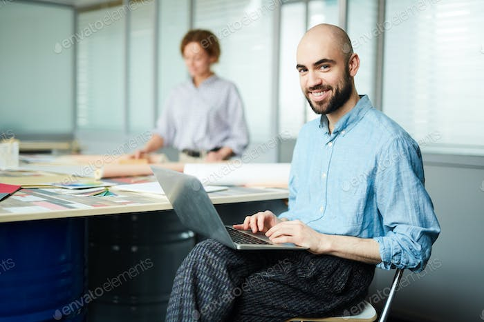 Cheerful web designer using laptop in open space office