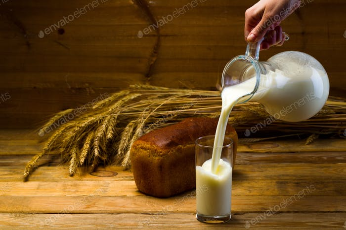 Milk from a glass jug poured into a glass, a loaf of rye bread, ears of corn