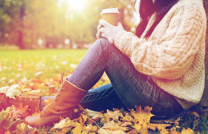 close up of  woman drinking coffee in autumn park