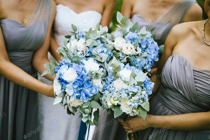 High angle view of bride and bridesmaids holding blue and white flower bouquets.
