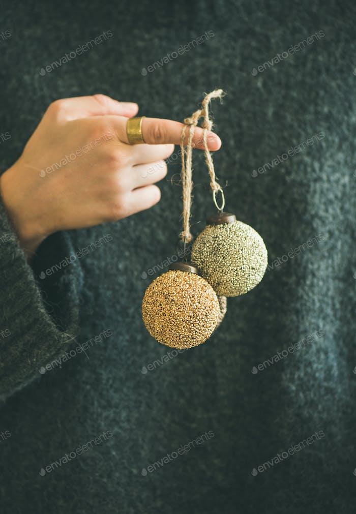 Frau in grauen Pullover mit dekorativen goldenen Kugeln auf dem Finger