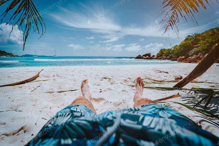POV shot of man wear blue swimming shorts laying on a beautiful sandy tropical beach Anse Cosos, La