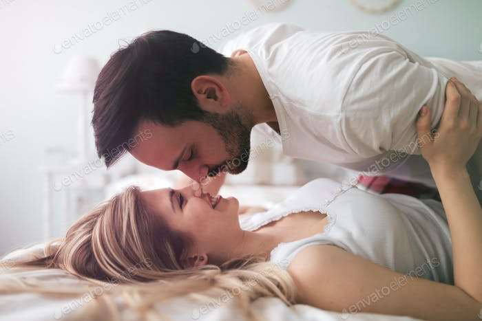 Sensual romantic foreplay by couple in bed