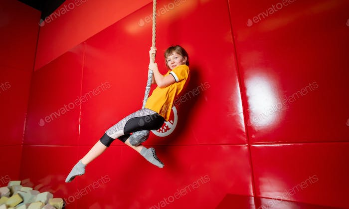 Happy child girl swinging on rope in indoor playground center