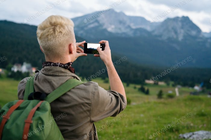 Young man with backpack taking a photo on the top of mountains