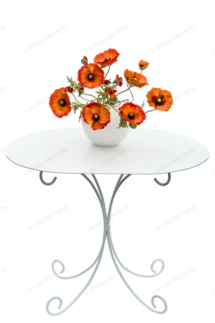 Vase with red poppies is on a coffee table, isolated on a white