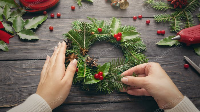 Female hands make Christmas wreath