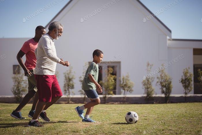 Junge spielt Fußball mit seinem Vater und Enkel