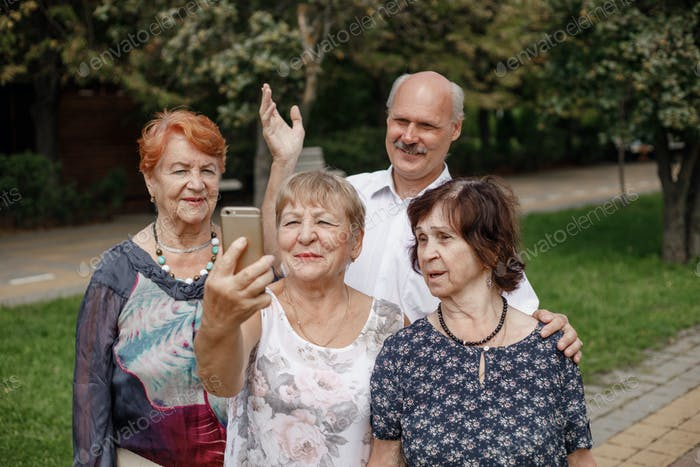 The group of smiling elderly people are making selfie together in a park on a warm day