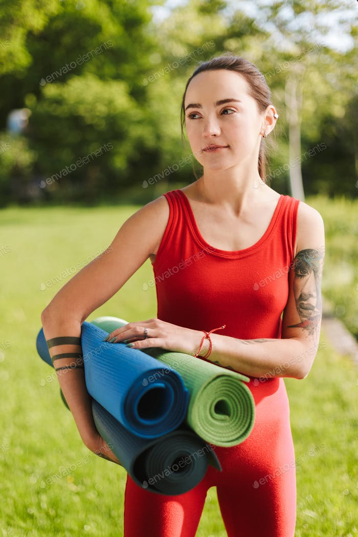 Young yoga trainer in red jumpsuit standing with yoga mats in hands and dreamily looking aside