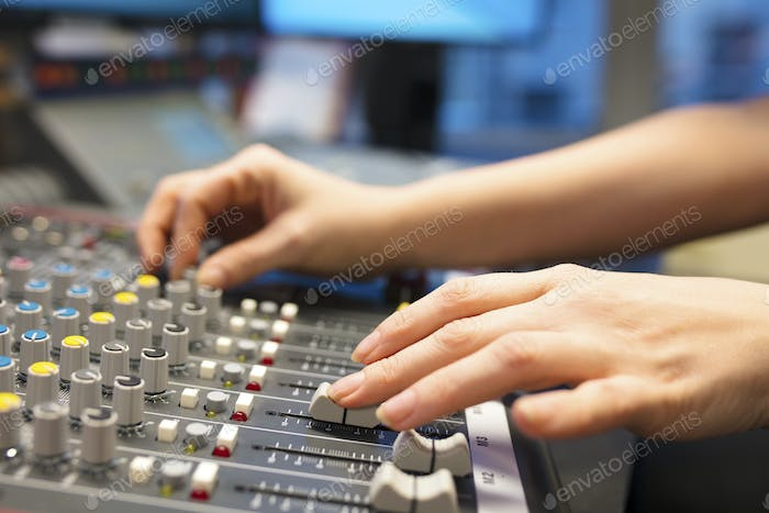 Female Radio Host Using Music Mixer In Studio
