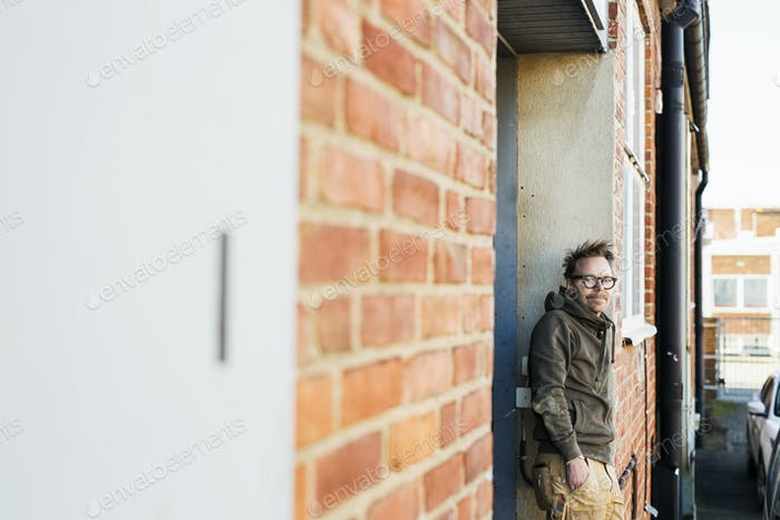 Portrait of carpenter leaning on brick wall