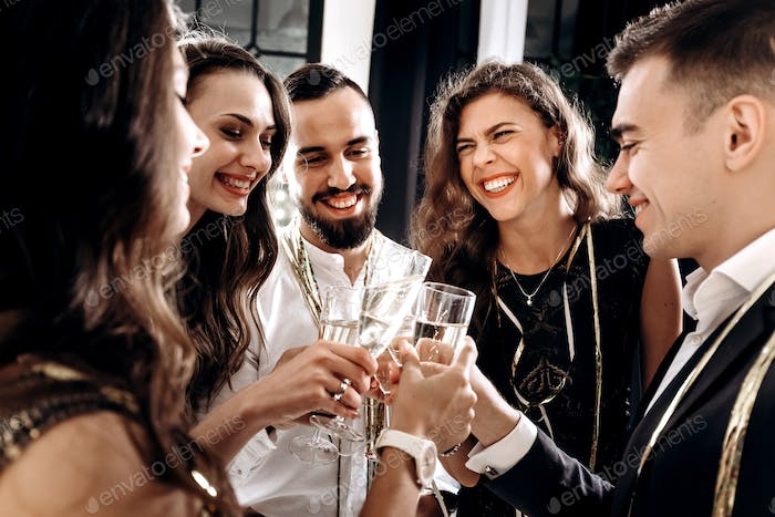Company of friends dressed in stylish elegant clothes stand together and clink glasses with