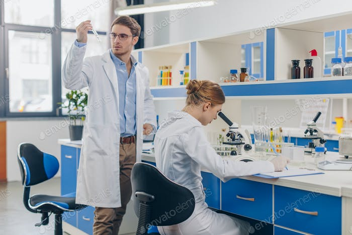 Biologen in weißen Mänteln arbeiten mit Röhren im Labor