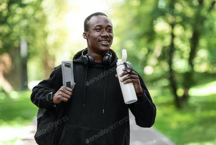 Balck Kerl in Sportkleidung halten Flasche mit Wasser