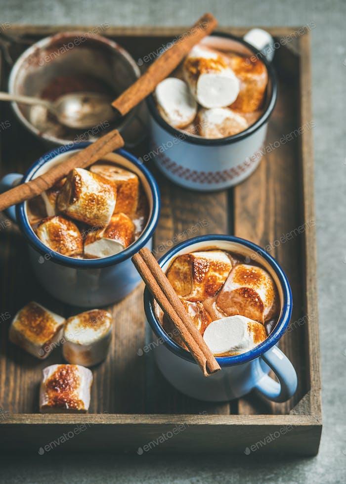 Heiße Schokolade mit Zimt und gerösteten Marshmallows in Holztablett