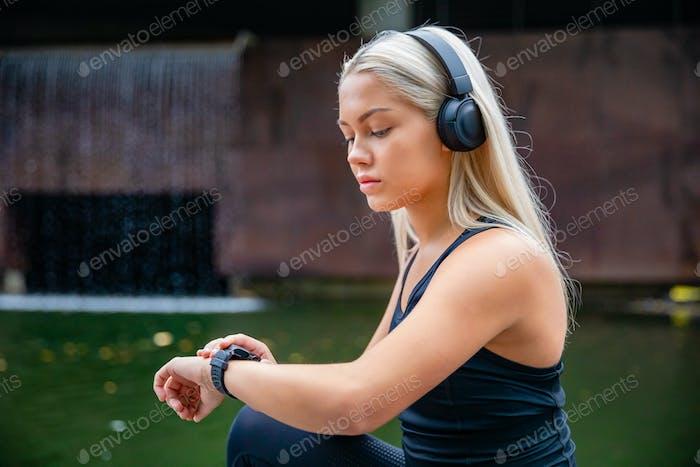 Sporty Female Runner Listening Music On Headphones While Using S
