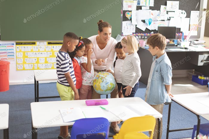 Overhead view of a schoolteacher discussing over the earth  globe in classroom at school